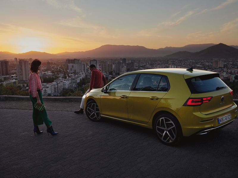 VW Golf, side view, stands on a mountain, in front of a couple