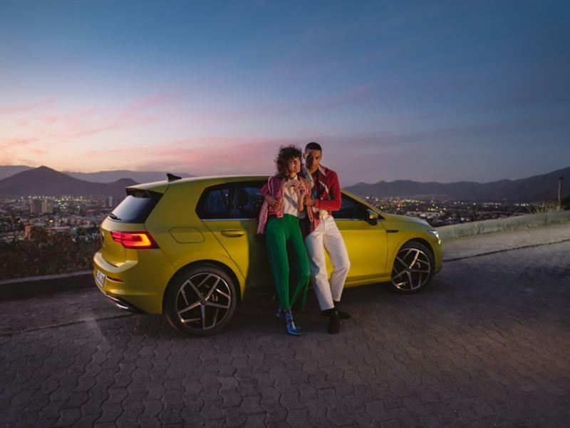 VW Golf, Seitenansicht, steht auf einem Berg , davor ein Pärchen