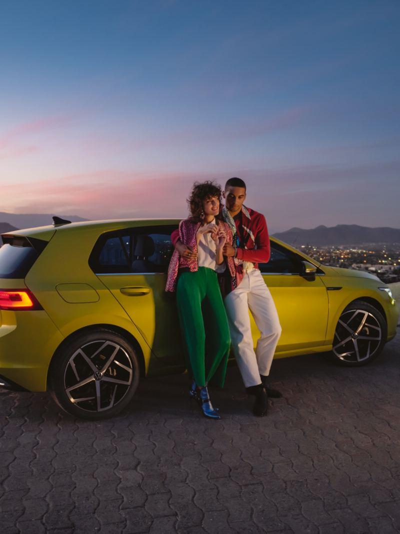 Vista lateral de um VW Golf, no topo de uma montanha, em frente a um casal