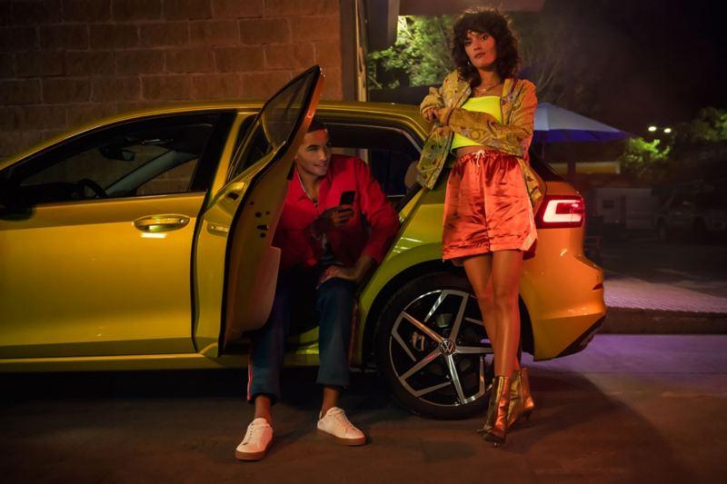 VW Golf Seitenansicht, ein Pärchen sitzt bzw. steht am Heck