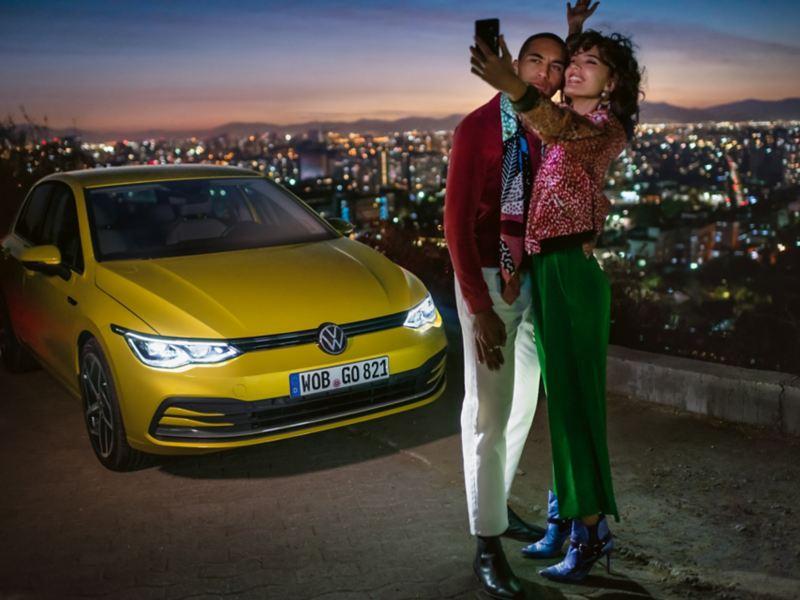 VW Golf,  3/4 Frontansicht, steht auf einem Berg , davor ein Pärchen, welches ein Selfie macht