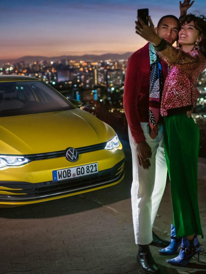 Vista 3/4 de frente do VW Golf, no topo de uma montanha, à sua frente encontra-se um casal que está a tirar uma selfie