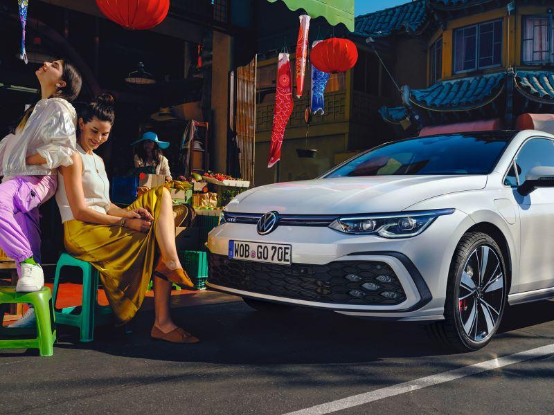 VW Golf GTE vue latérale est dans une rue, devant 2 femmes