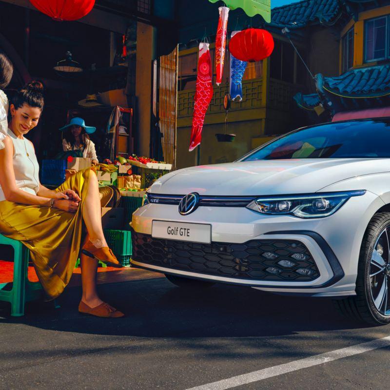 Volkswagen Golf 8 GTE, vista lateralmente, con due donne sedute a fianco.