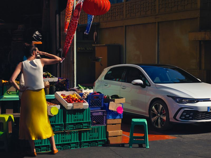 VW Golf GTE in white, front side view, stands next to a vegetable stand, a woman stands in front of it