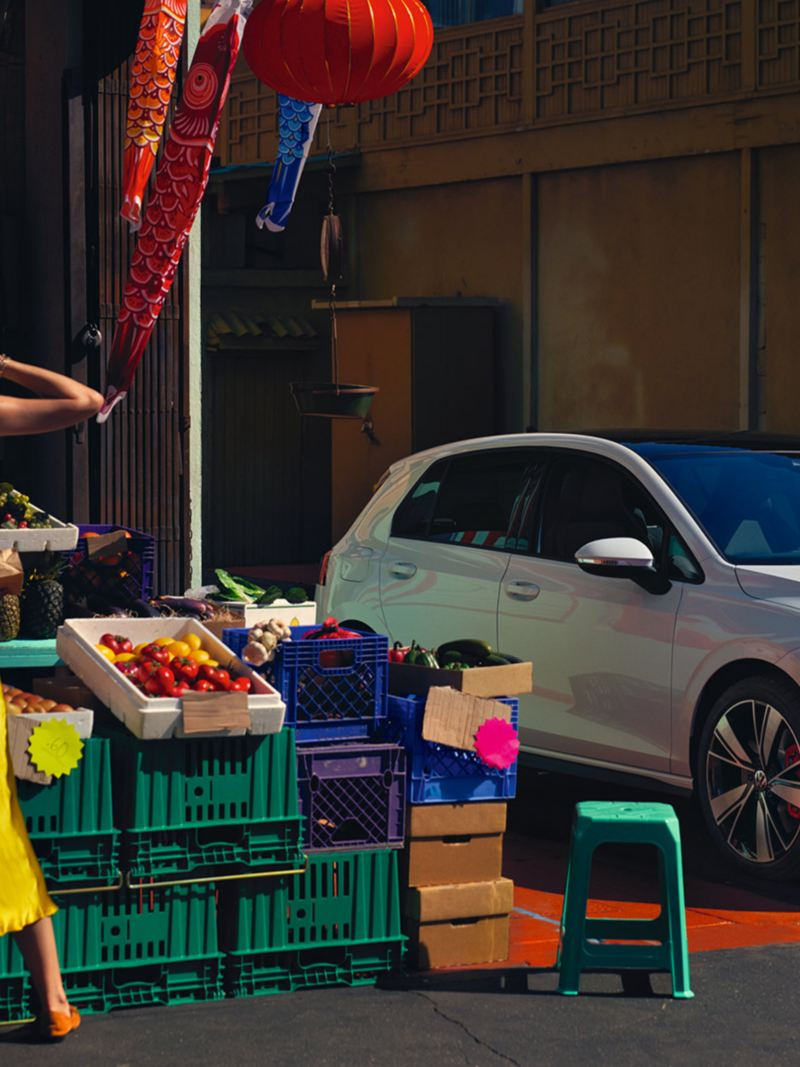 VW Golf GTE in white, front side view, stands at a vegetable stand, in front of it stands a woman
