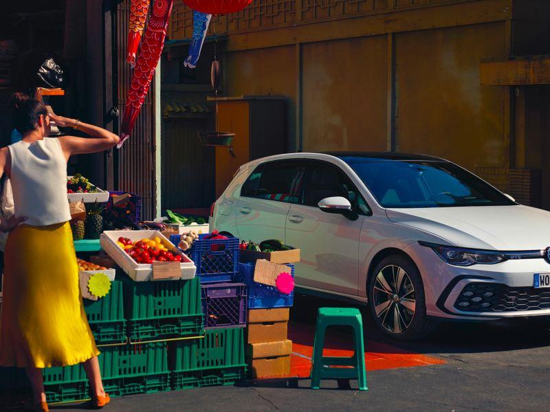 Vista laterale di Volkswagen Golf 8 GTE parcheggiata vicino ad un negozio dove una donna sta guardando la merce esposta