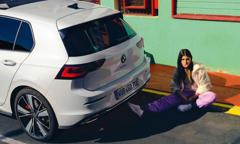 VW Golf GTE in white, rear view, stands on a street, next to it sits a woman