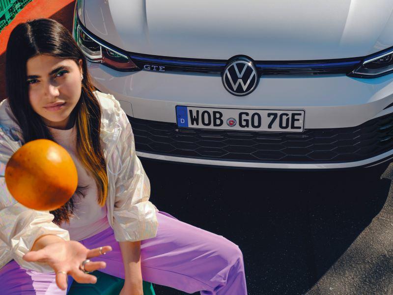 Une femme lance une orange devant la Golf GTE