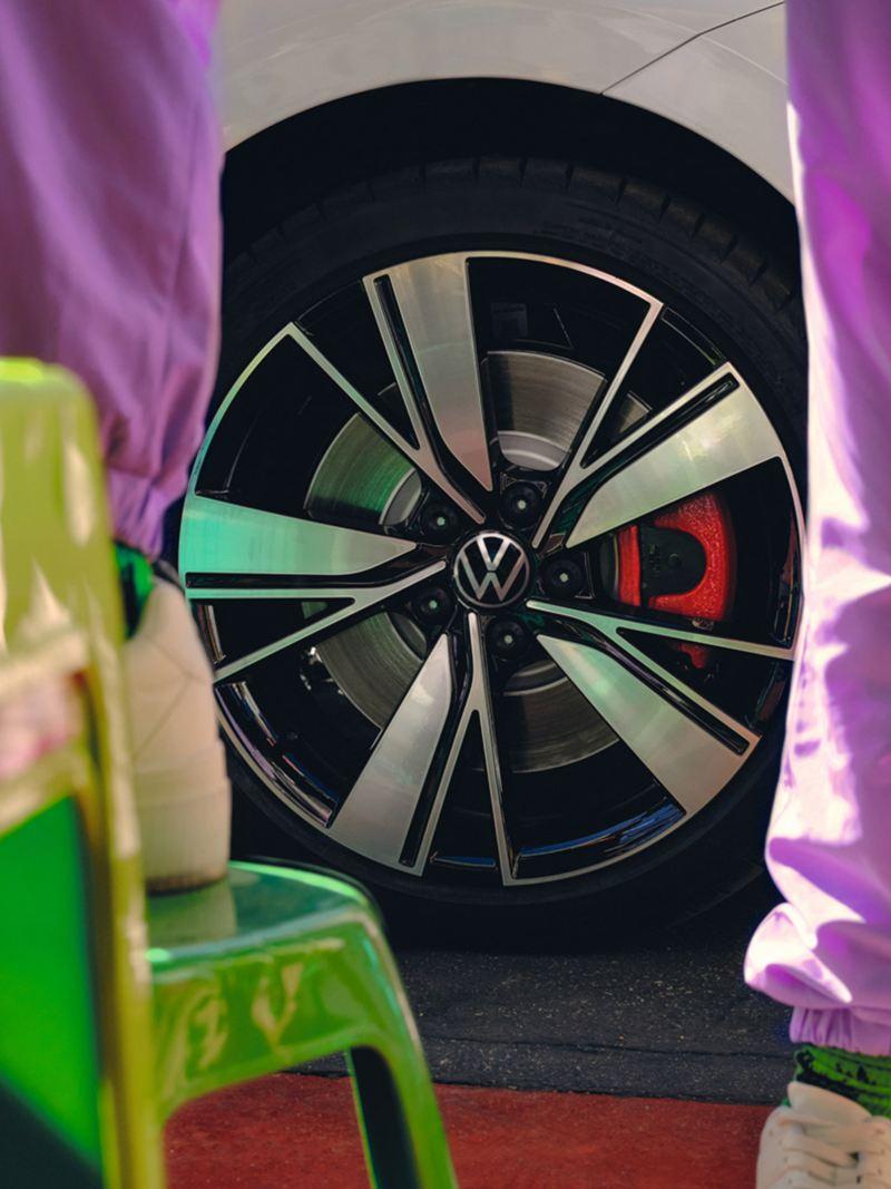 VW Golf GTE blanche, détail de la jante Bakersfield 18 pouces, jambes dans un survêtement rose en premier plan