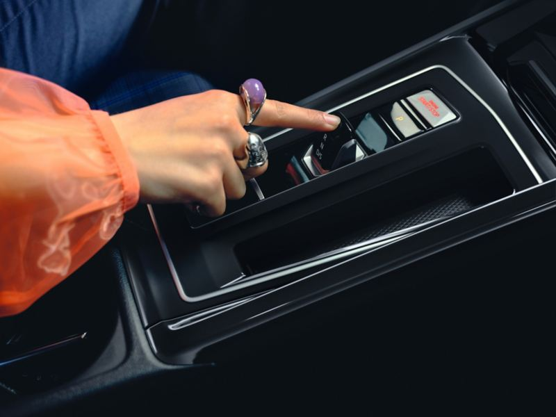 VW Golf GTE, a woman's hand operates the toggle switch on the DSG dual clutch transmission