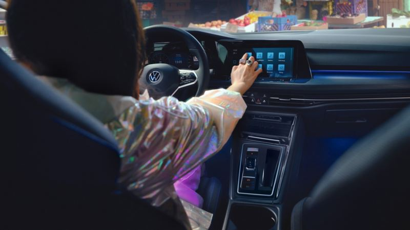 VW Golf GTE Interior, view into the cockpit, woman operates the infotainment system's touchscreen