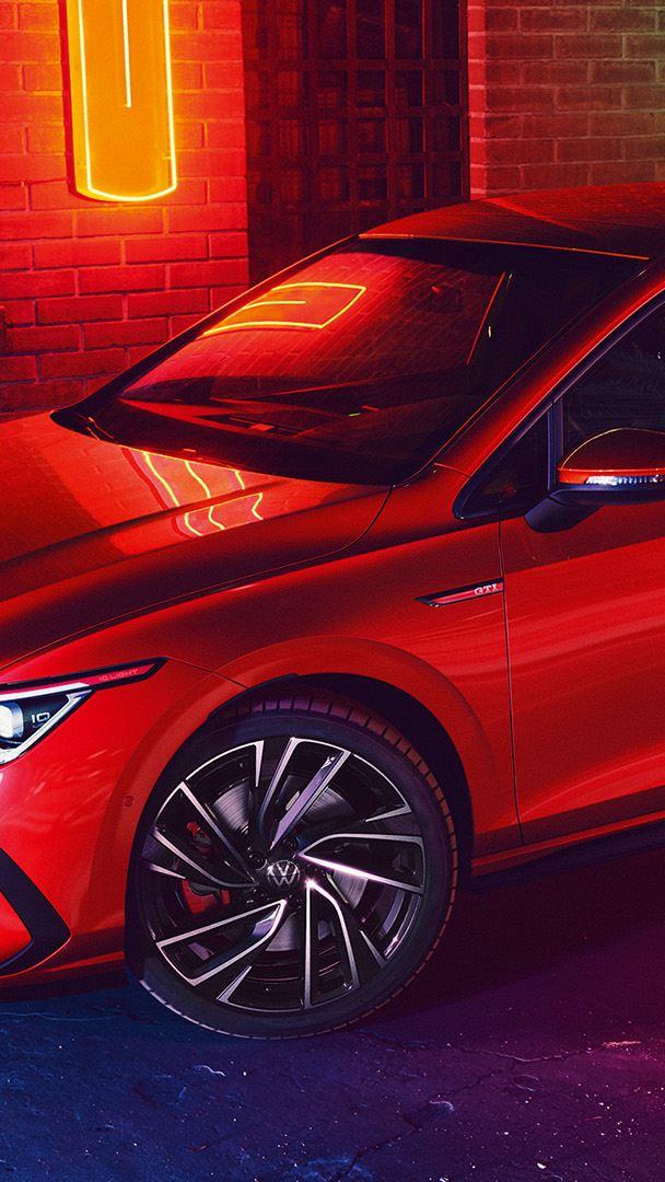 VW Golf GTI in Rot, Seitenansicht, steht nachts auf einer Straße vor einem rot angeleuchteten Gebäude.