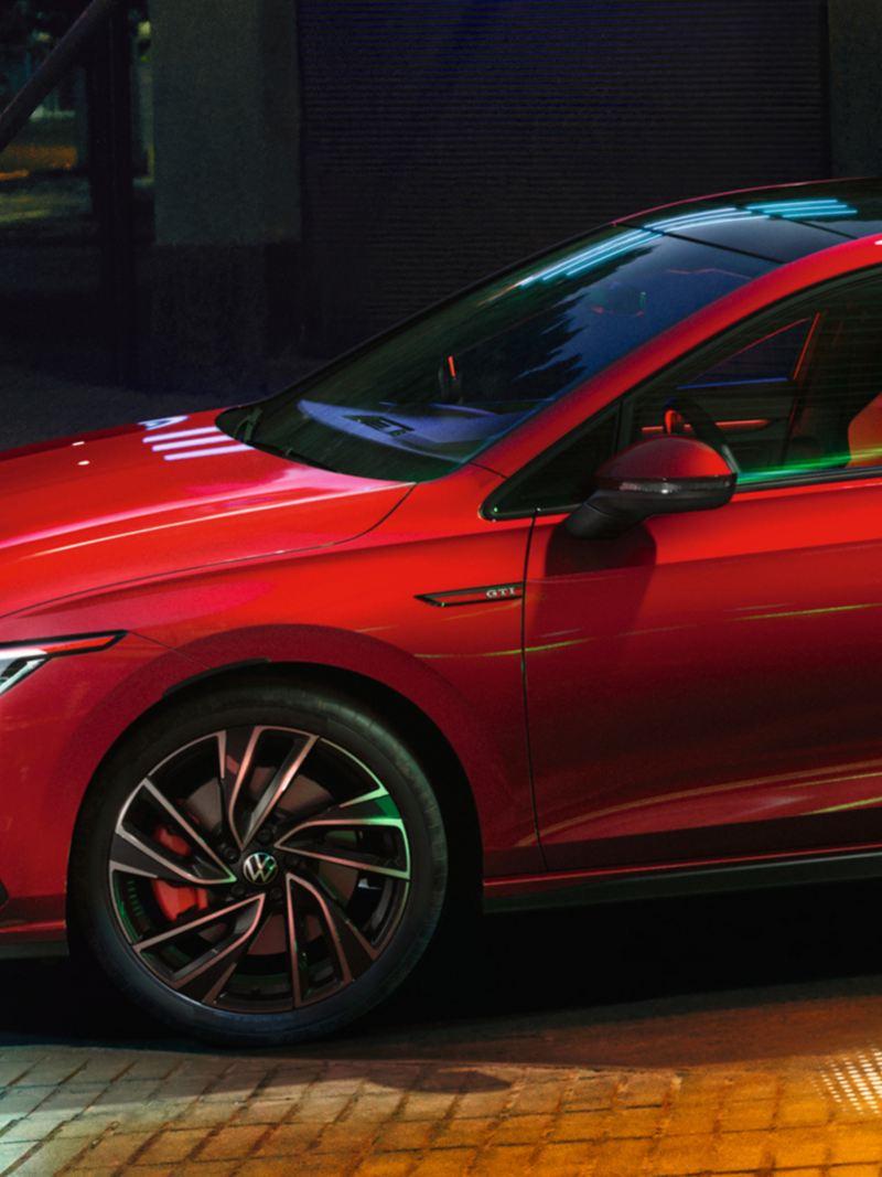 VW Golf GTI in rot, Seitenansicht, leuchtstarke IQ.Light-Scheinwerfer, leuchtstarke Außenumgebungsbeleuchtung