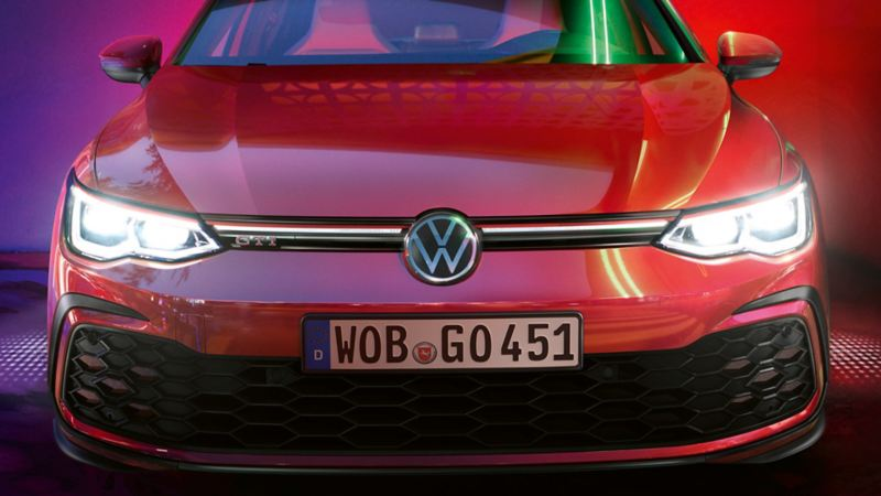 A white Golf GTI with red accents and a stylish front spoiler – Volkswagen sport and design products