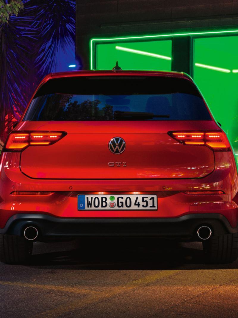 VW Golf GTI in Rot, Rückansicht, vor einem Club geparkt