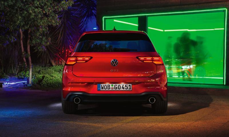 VW Golf GTI in Rot, Heckansicht, steht vor einem Club