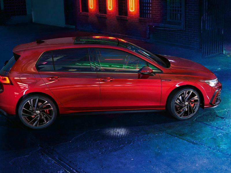 VW Golf GTI in red, side view, parked in a warehouse