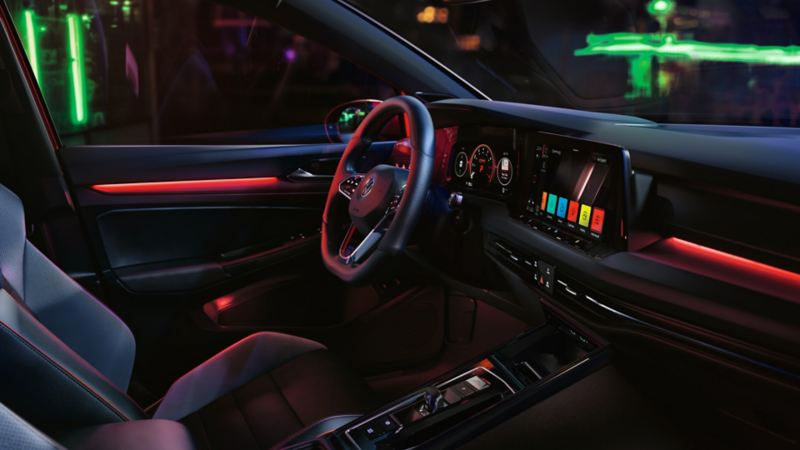 VW Golf GTI interior, cockpit view, woman operating infotainment system