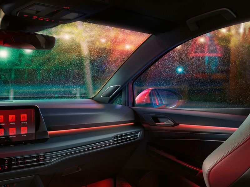 VW Golf GTI interior, cockpit with red ambient lighting, focus on the passenger's seat