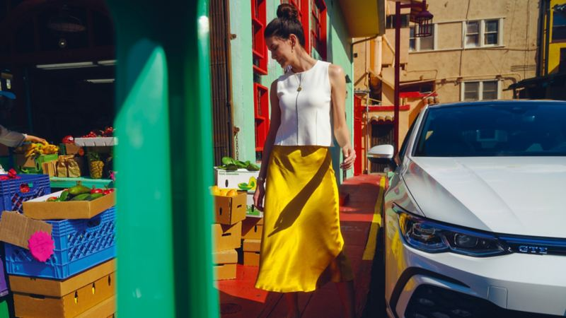 VW Golf GTE in Weiß, Frontansicht angeschnitten, steht bei einem Gemüsestand, daneben steht eine Frau