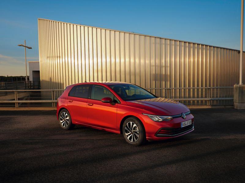 Roter VW Golf ACTIVE parkt vor einer beigen Wand. Blick auf Front, Räder und Seite.