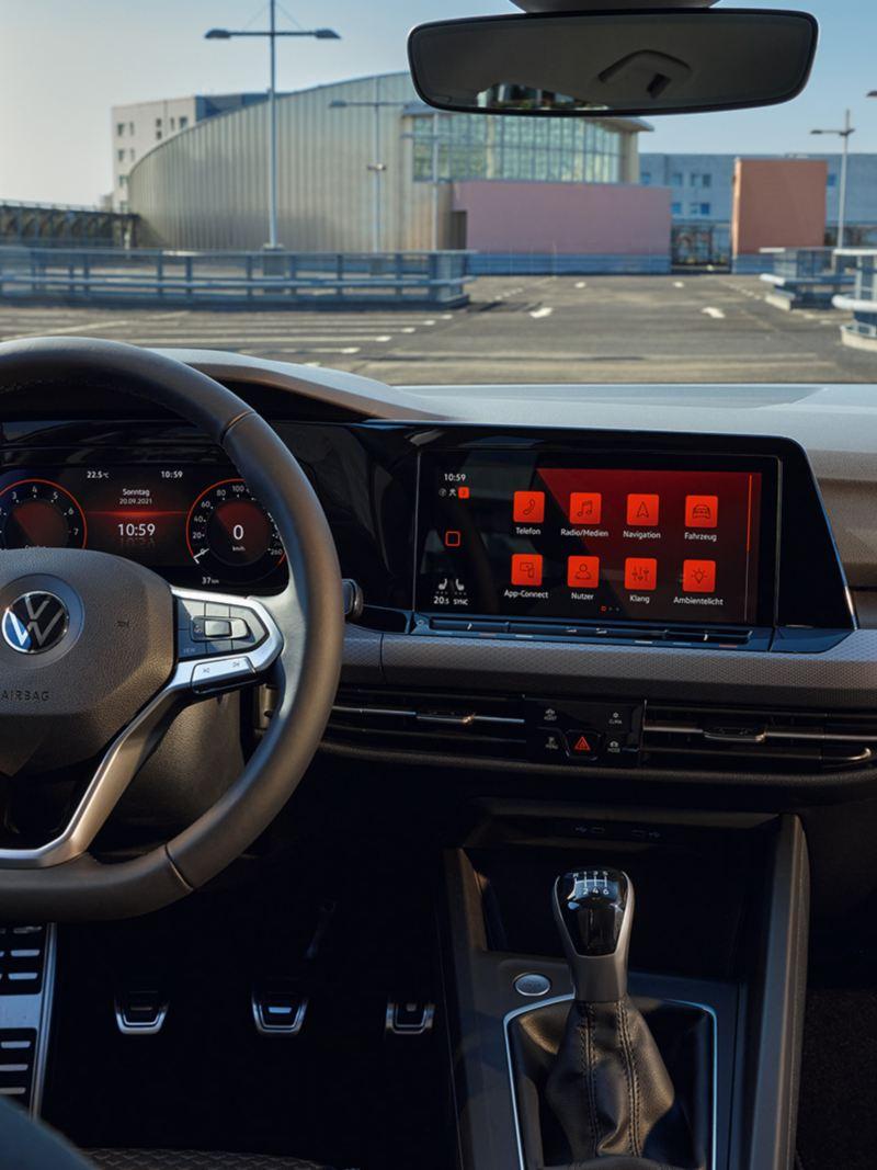 Roter VW Golf ACTIVE von innen. Blick im Cockpit auf Multifunktionslenkrad, Pedalkappen und Armaturen mit Ambientebeluchtung