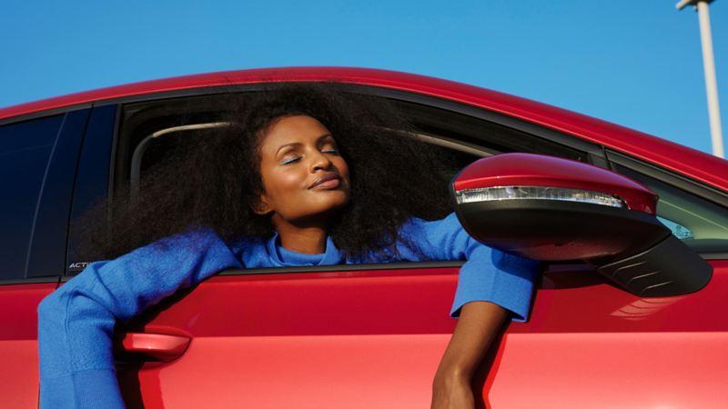 Roter VW Golf ACTIVE mit geöffnetem Fenster. Frau mit blauem Pullover lehnt sich heraus.