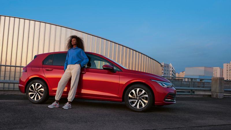 Roter VW Golf ACTIVE parkt vor einer beigen Wand. Eine Frau lehnt gegen die Seite des Autos.