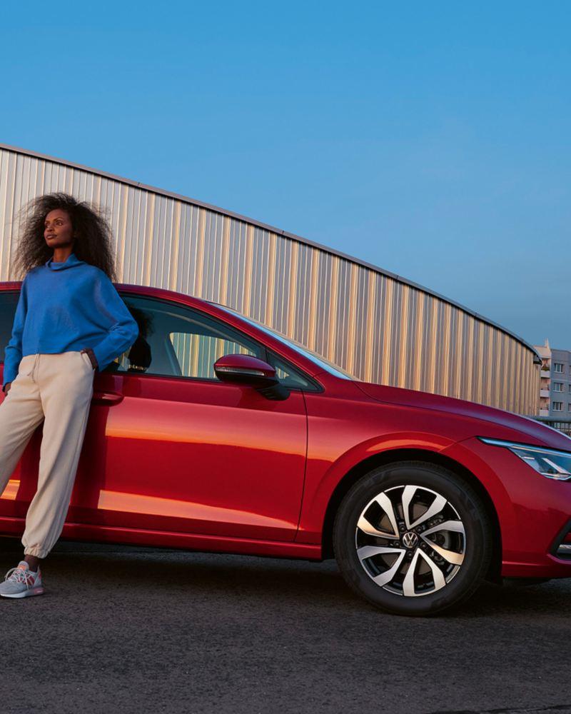 Une VW Golf ACTIVE rouge garée devant un mur beige. Une femme s'appuie sur le côté de la voiture.