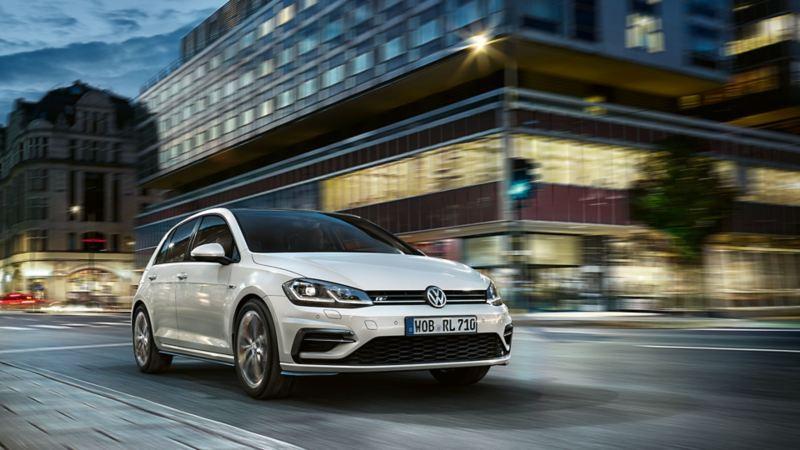 VW Golf jedzie o zmroku przez miasto, widok od przodu