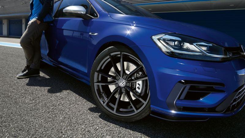 VW Golf R met iemand die ertegenaan leunt; detailbeeld schuin vooraan, met koplampen, velgen en kleurcontrasterende buitenspiegels