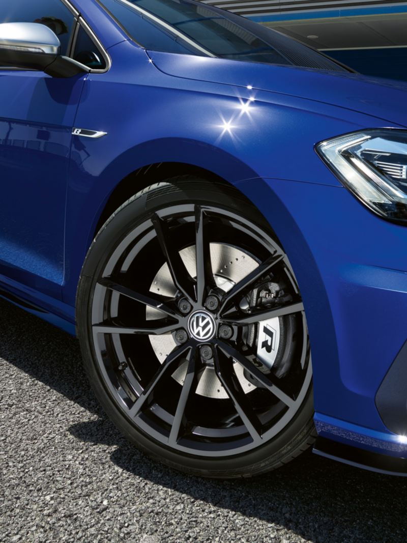 A man is leaning against a VW Golf R