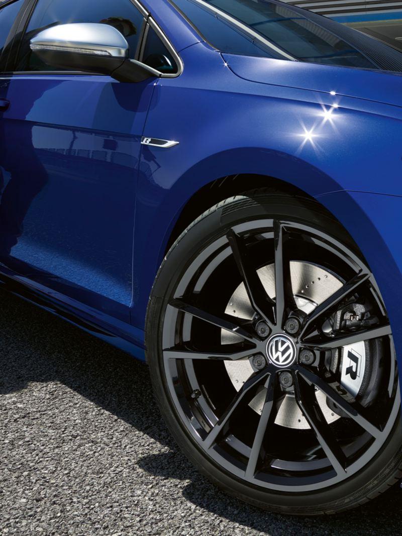 Wycinek boku frontu VW Golfa R Variant, o który opiera się osoba, z reflektorami, felgą i kontrastowymi lusterkami zewnętrznymi