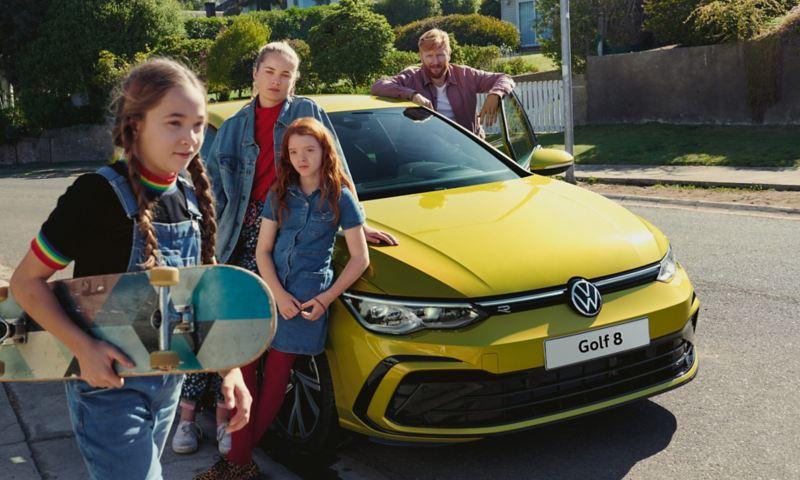 famiglia attorno a VW Golf 8 parcheggiata