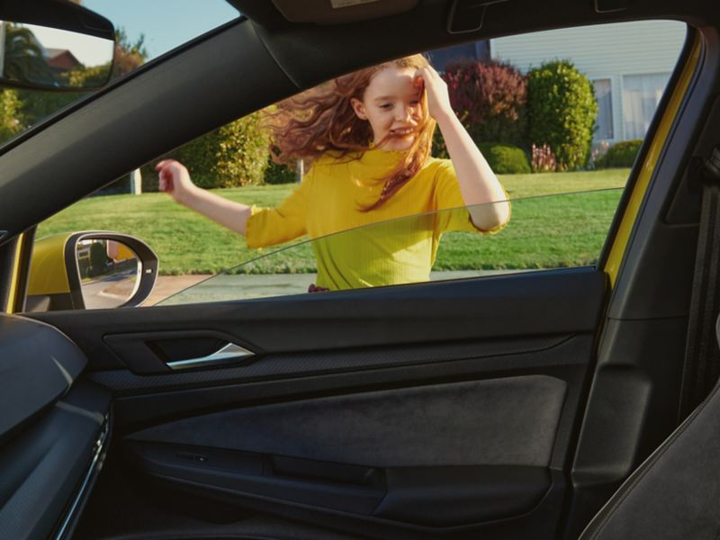 Ett barn utanf;r en Volkswagen Golf