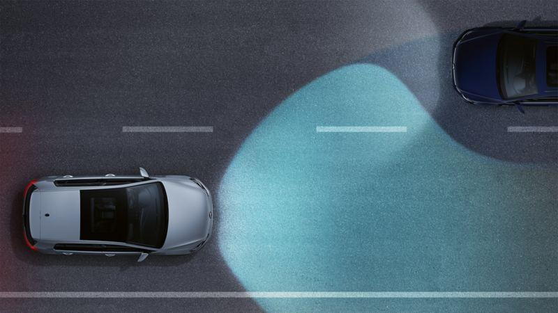 Ein Volkswagen bei Nacht auf einer Straße von oben betrachtet. Man sieht die Fernlichtregulierung als Lichtkegel