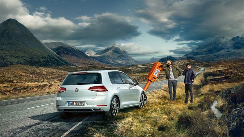 VW Golf a bordo strada, due uomini in piedi vicino a una colonnina del soccorso stradale