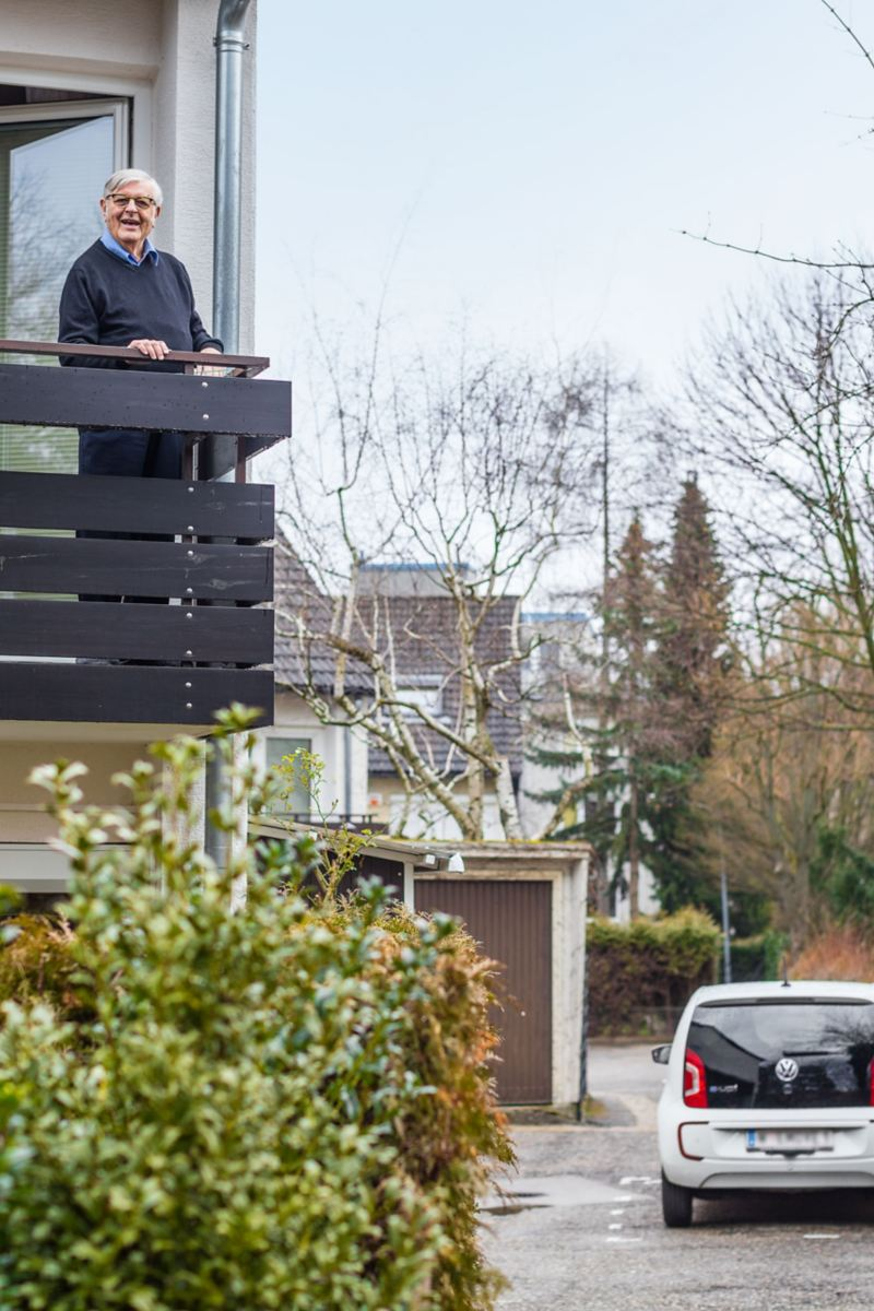 Gerhard Heinz standing on his balcony and watching his e-up! charging with a wallbox in his driveway