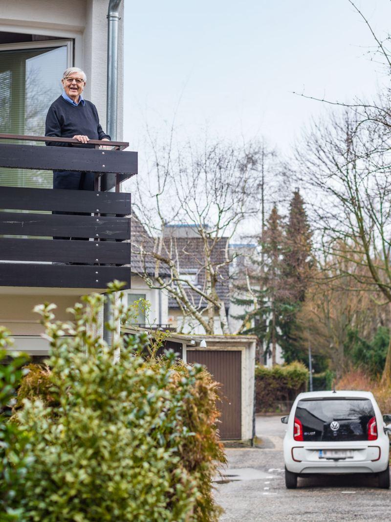Gerhard Heinz est sur son balcon et observe sa e-up! en train de se recharger sur la Wallbox