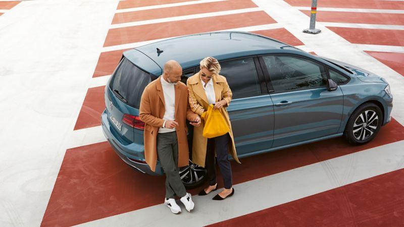 Un couple s'appuie contre une Golf Sportsvan IQ.DRIVE