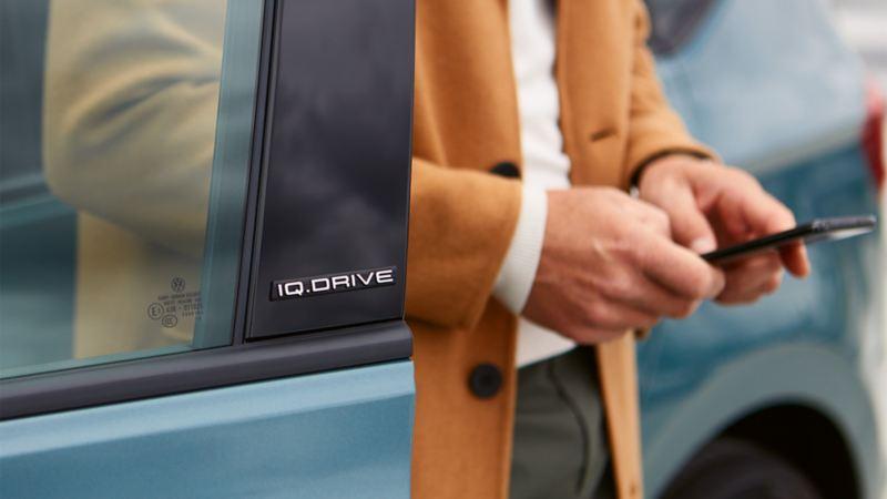 Un homme avec un smartphone se tient dans l'ouverture de porte d'une Golf Sportsvan IQ.DRIVE.