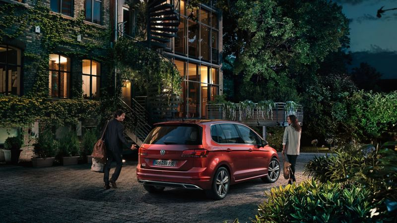 VW Golf Sportsvan steht vor einem Haus, eine Mann und eine Frau stehen vor dem Auto