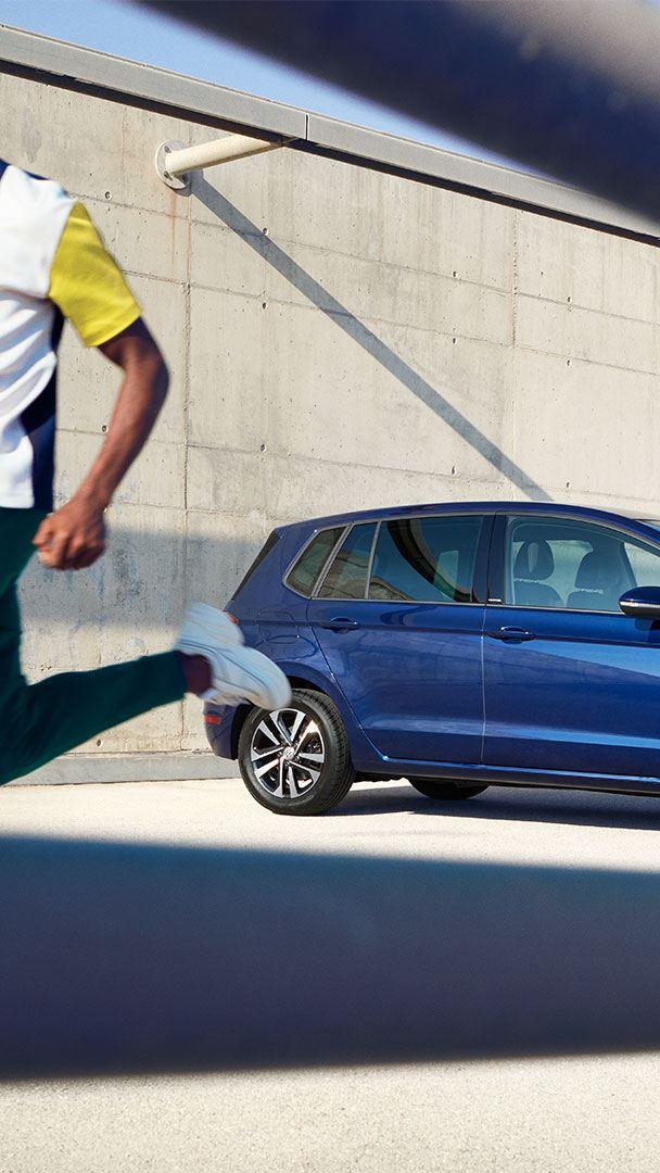 Mann enfernt sich joggend vom VW Golf Sportsvan UNITED