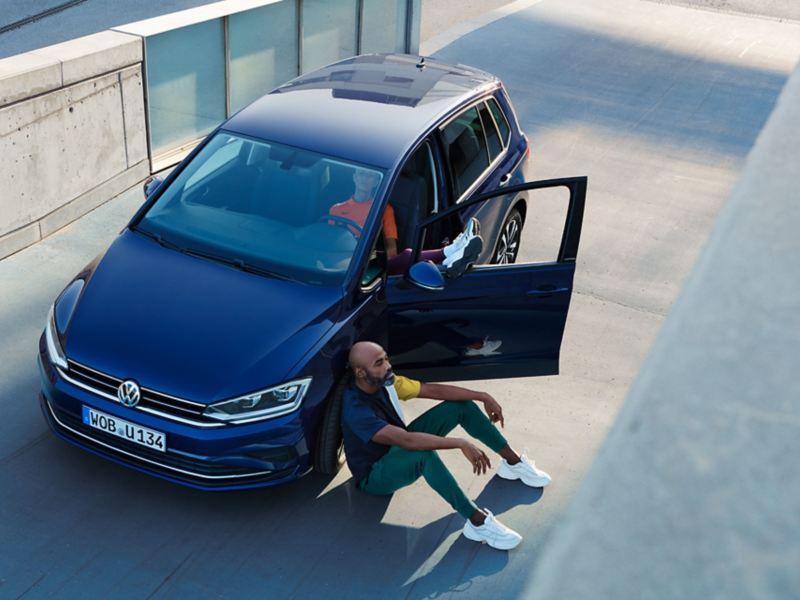 VW Golf Sportsvan UNITED Front mit offener Tür, Mann sitzt davor Vorderrad