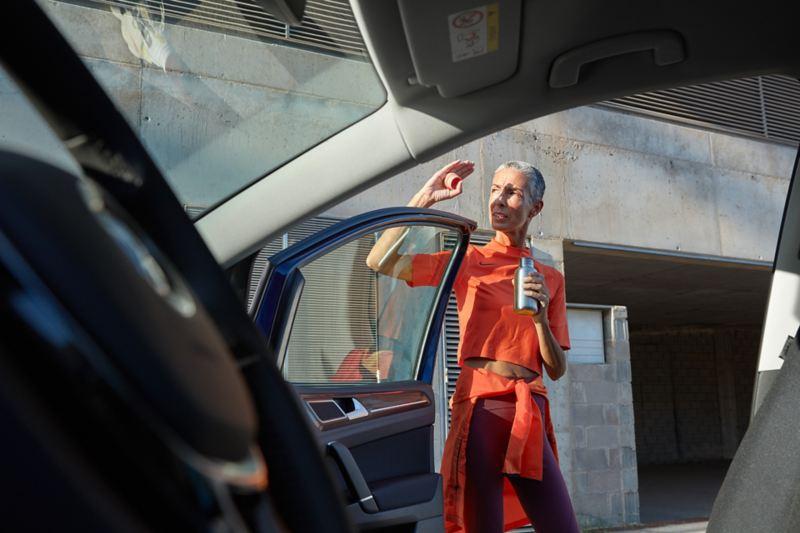 Blick aus der Beifahrertür eines VW Golf Sportsvan auf eine sich vor Blendung der Sonne schützenden Frau