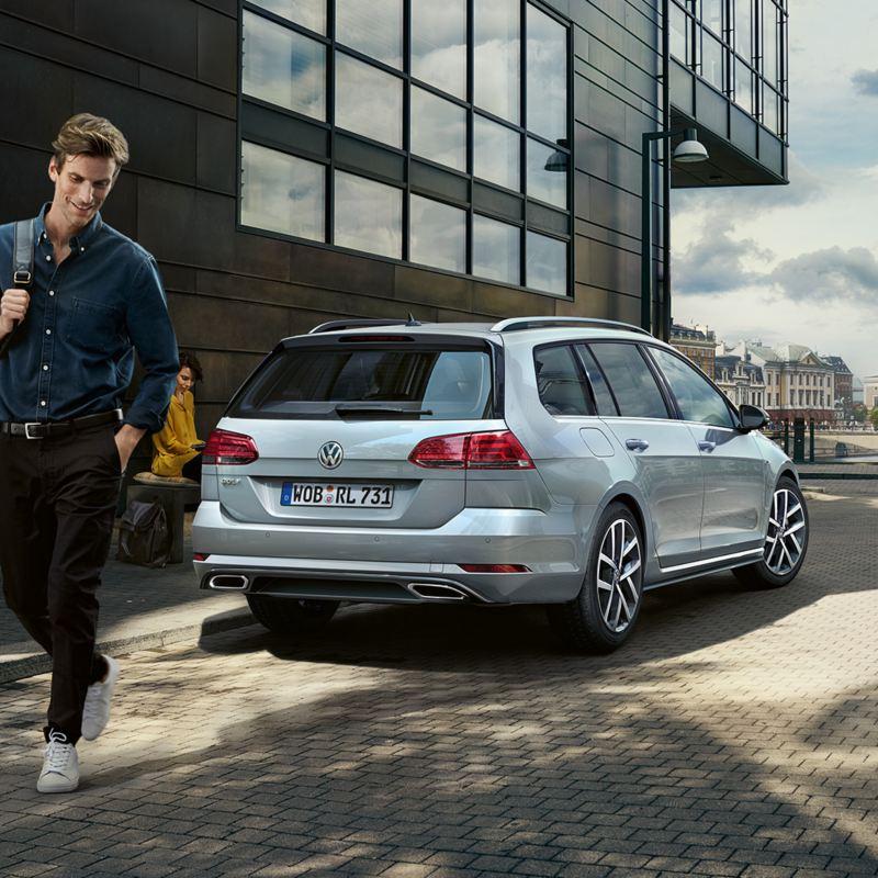 Uomo si allontana da Volkswagen Golf Variant a metano vista posteriore ferma in città