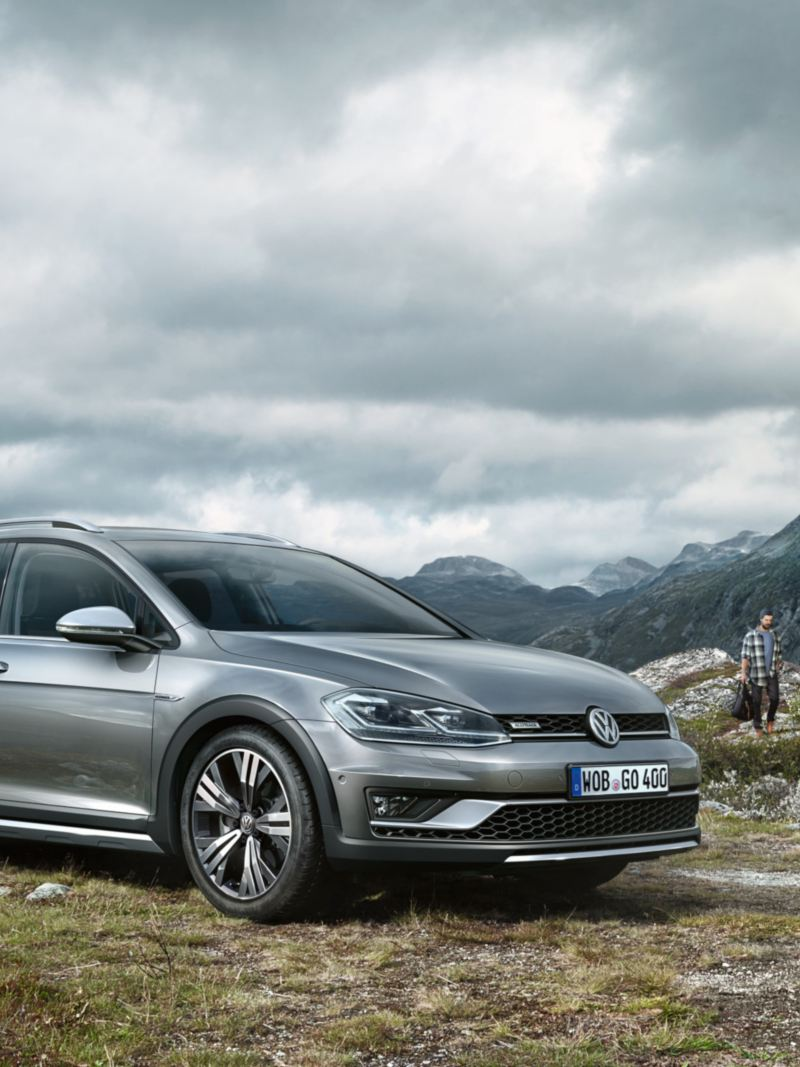 The VW Golf Alltrack standing on a plateau with mountains in the background
