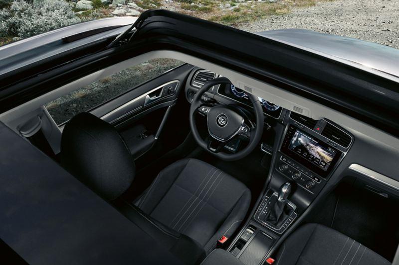 Zdjęcie od góry do wnętrza VW Golfa Alltrack przez otwarty dach panoramiczny