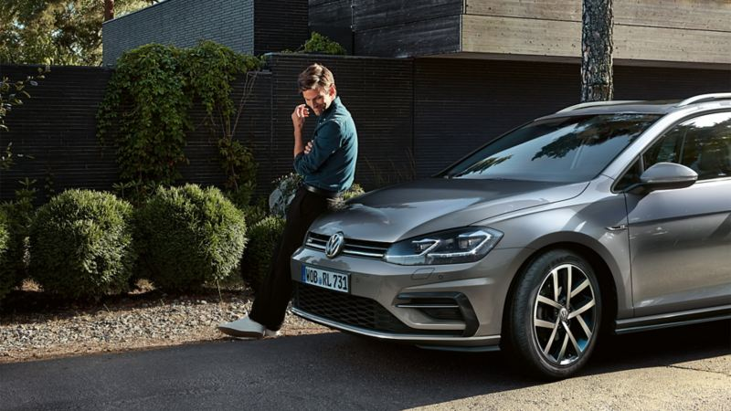 Uomo seduto sul cofano di VW Golf Variant TGI a metano